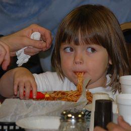 young girl eating spaghetti